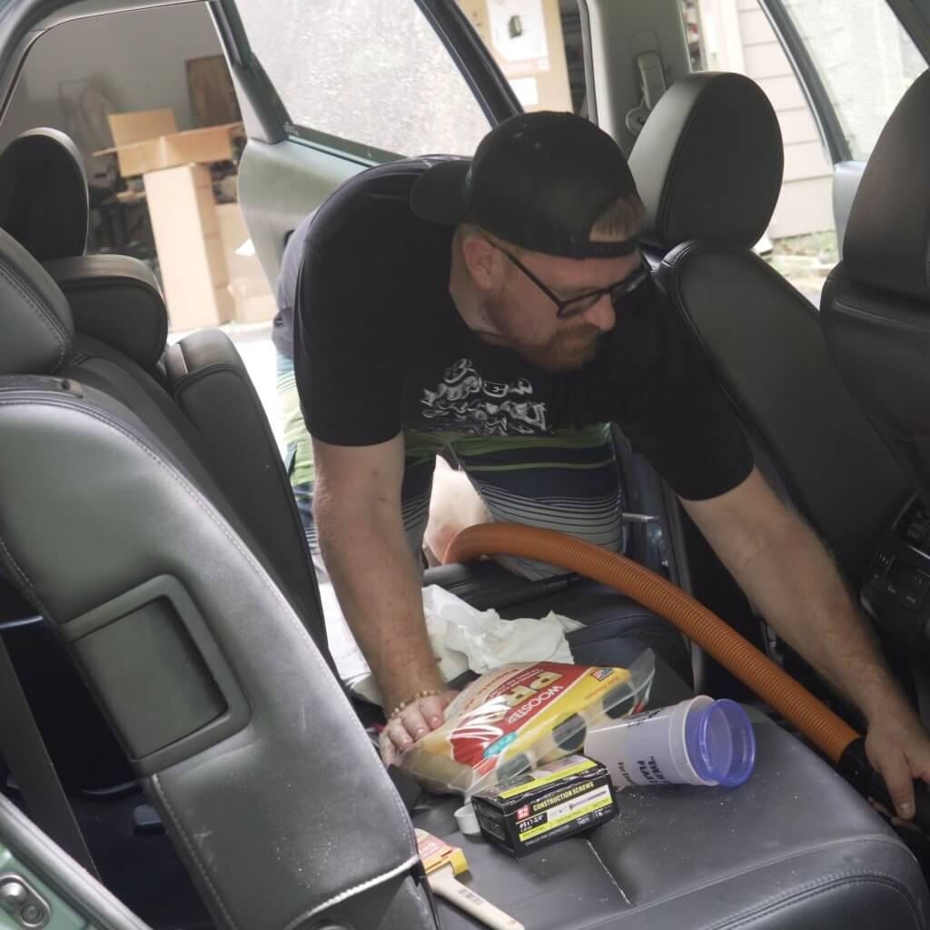 Rick cleaning back seat with Ridgid NXT line of wet/dry vac